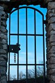 pic of mountain chain  - Old door with metal grill locked with a chain - JPG