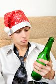 foto of sad christmas  - Sad and Tired Teenager with Bottle of the Beer and Santa Hat on the Sofa at the Home - JPG