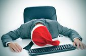 picture of christmas party  - a man in suit with a santa hat sleeping in his desk after an office christmas party - JPG