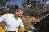 stock photo of shingles  - Man wearing work gloves taking shingles off roof - JPG