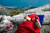 pic of sleeping bag  - Young woman taking selfie photo in red sleeping bag on the rocky mountain - JPG