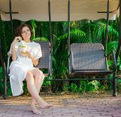 stock photo of swingset  - Woman drinks fresh coconut on the swinset - JPG