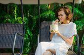 foto of swingset  - Woman drinks fresh coconut on the swinset - JPG