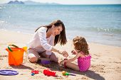 foto of babysitter  - Young Latin mother and her little girl using sand to build a castle at the beach - JPG