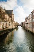 stock photo of row houses  - The Church of Our Lady and a row of canal houses in the Dutch city of Dordrecht - JPG