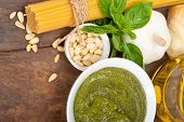 foto of virginity  - Italian traditional basil pesto pasta ingredients parmesan cheese pine nuts extra virgin olive oil garlic on a rustic table - JPG