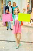 image of mall  - Cheerful family shopping in shopping mall while little girl showing her shopping bags and smiling - JPG