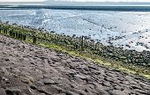 stock photo of dike  - Grey green and blue colored landscape with a dike of basalt stones and tar covered with algae and salt marshes that reflect the blue sky.
