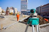 image of geodesic  - Surveying measuring equipment level transit on tripod at construction building area site - JPG