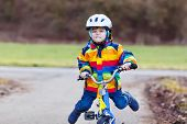 stock photo of four-wheel  - Funny cute preschool kid boy in safety helmet and colorful raincoat riding his first bike and having fun on cold day outdoors - JPG