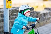pic of traffic light  - Little preschool kid boy riding with his first green bike in the city - JPG