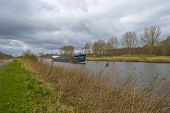 foto of barge  - Barge sailing in a canal under a cloudy sky in spring