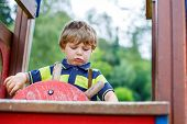 picture of imaginary  - Funny kid boy pretends driving an imaginary car on children playground outdoors - JPG