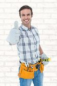 picture of handyman  - Happy handyman gesturing thumbs up against white wall - JPG