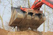 stock photo of wheel loader  - A tilt wheel excavator with a shovel earth on a mountain  - JPG
