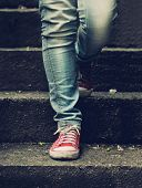 foto of skinny girl  - Little girl in red sneakers and jeans making first step on the stairs - JPG