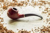 picture of tobacco leaf  - Tobacco pipe on rustic warn wood surface with spilled natural tobacco - JPG