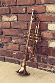 picture of trumpets  - Old worn trumpet stands alone against a brick wall outside a jazz club - JPG