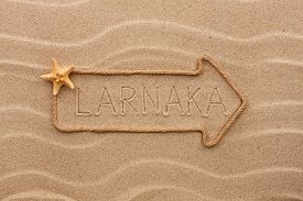 picture of larnaca  - Arrow made of rope and starfish with the word Larnaca on the sand as background - JPG