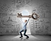 stock photo of keyhole  - Young man and keyhole at background lifting big key above head - JPG