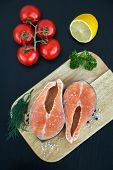 pic of salmon steak  - upper view of two salmon steaks on a wooden board with lemon and tomato - JPG