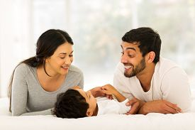 picture of indian  - happy young indian family lying on bed - JPG