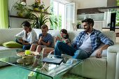 Family using laptop and mobile phone in living room at home poster