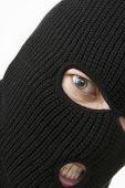 image of shoplifting  - evil angry criminal wearing black military mask - JPG