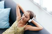 10 years old tween girl relaxing on a couch, listening to music in headphones and playing with table poster