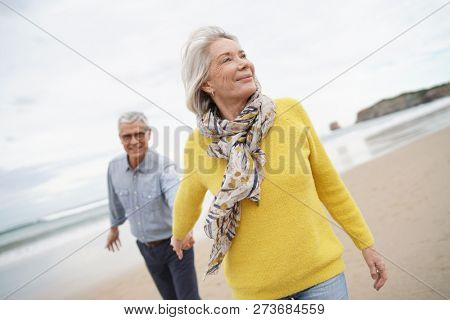 poster of  Vibrant senior woman holding husband's hand and leading the way on beach walk