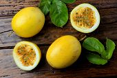 Yellow Passion Fruit With Leaves And Passion Fruit Cut In Half On Rustic Wooden Table poster