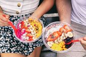 Acai bowl and pitaya dragonfruit smoothie healthy breakfast bowls young friends eating together. Cou poster