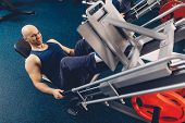 Happy Male Doing Exercise On Training Apparatus. Physical Training Of A Man On A Training Apparatus  poster