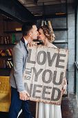 Loving Couple Kissing Holding Signboard All You Need Is Love. poster