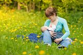 foto of mother baby nature  - Little baby girl breast feeding outdoor - JPG