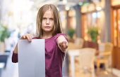 Young beautiful girl holding blank sheet paper over isolated background pointing with finger to the  poster