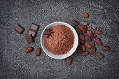 .top View Of Cocoa Powder In White Bowl With Pieces Of Chocolate Bar And Cocoa Beans poster