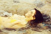 Pretty Happy Girl Or Beautiful Woman With Wet Hair In Sexy Yellow Swimsuit Lying In Transparent Sea  poster