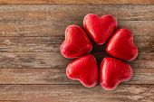 valentines day, sweets and confectionery concept - close up of red heart shaped chocolate candies on poster