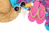 Beach accessories with straw hat, bottle of balm solar,sun glasses,shawl and flip flops on white bac