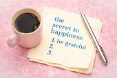 the secret to happiness concept - handwriting on a napkin with a cup of espresso coffee poster