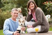 Постер, плакат: Пара с Pet собаки на открытом воздухе наслаждаясь напитком в саду паб