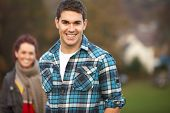 stock photo of teenage boys  - Teenage Boy Outside With Girlfriend In Background - JPG