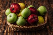 Wicker Basket With Delicious Red, Green And Yellow Apples On Wooden Table poster