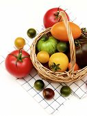 Fresh Organic Colorful Tomatoes In Wicker Basket On Checkered Napkin Isolated On White Background poster
