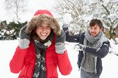 stock photo of snowball-fight  - Young couple having snowball fight - JPG