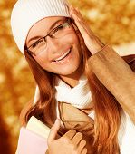 Picture of cute cheerful student girl in university autumn park, portrait of happy smiling teenager