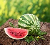 image of watermelon slices  - Watermelon with a slice and leaves on a wooden table - JPG