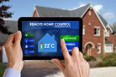 stock photo of electricity  - Holding a smart energy controller or remote home control online home automation system on a digital tablet - JPG