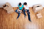 stock photo of married  - overhead view of couple sitting on floor together using computer wireless internet while moving into new home - JPG